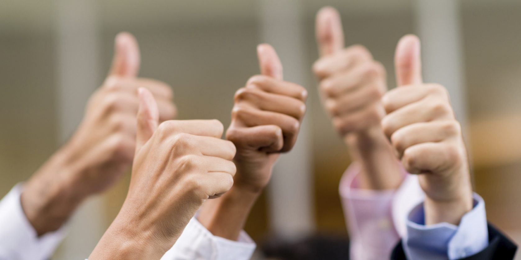 Business group with thumbs up expressing positivity